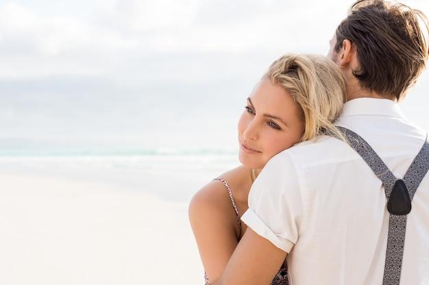 ビーチで彼氏を抱きしめる若い女性の顔をクローズアップ