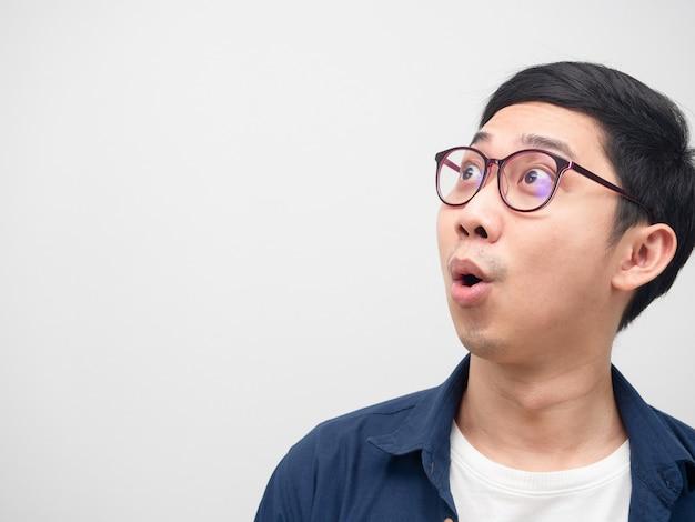 Крупным планом лицо азиатского мужчины в очках, чувствуя себя изумленным, глядя на копию пространства на белом фоне
