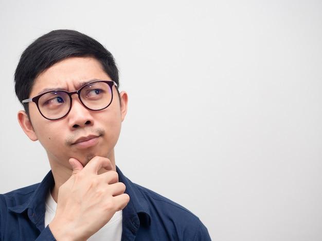 Крупным планом лицо азиатского человека в очках, думающего и смотрящего на копию пространства на белом фоне