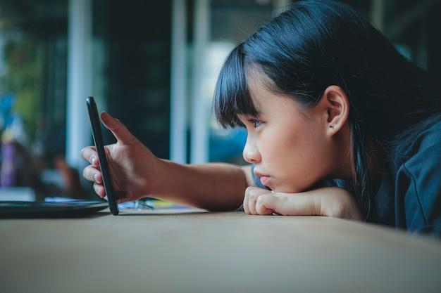 手にスマートフォンの画面を見ているアジアのティーンエイジャーの顔をクローズアップ