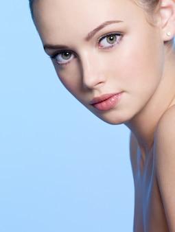 Крупным планом лицо красивой молодой женщины со свежей кожей