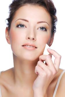 フェイスファンデーションを適用する美容若い女性のクローズアップ顔