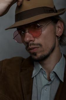 Крупным планом лицо жестокого молодого человека в модных круглых очках в элегантной ретро-одежде в винтажной шляпе в студии у серой стены. бородатый парень в помещении. старомодный стиль. элегантная мужская одежда.