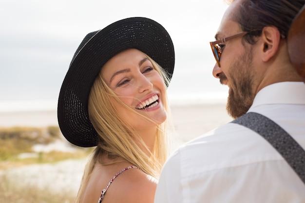 屋外の男と笑っている陽気な若い女性の顔をクローズアップ