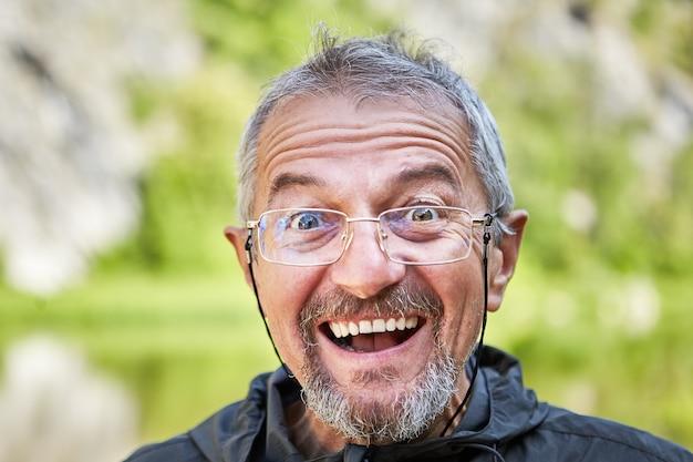작은 수염을 입고 레이스에 얇은 금속 프레임이있는 안경에 기뻐하거나 놀란 남자의 클로즈업 얼굴.