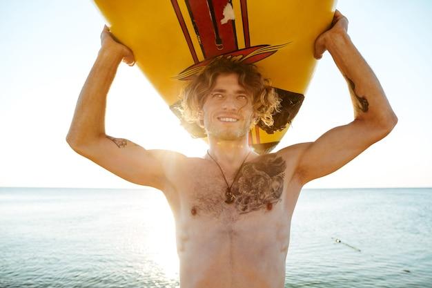 해변에서 머리에 서핑 보드와 잘 생긴 웃는 곱슬 남자의 얼굴을 닫습니다