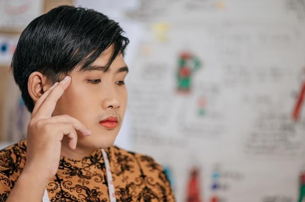 スタジオで考えている首に巻尺でプロのアジアの若い男性の仕立て屋の顔をクローズアップ。