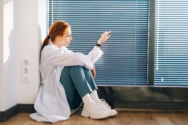루브르 박물관을 열고 블라인드를 통해 햇빛을 바라보는 슬픈 불행한 여성 의사의 클로즈업 얼굴. 좌절한 젊은 여성 의사는 직업적인 실수에 대해 걱정하고 있습니다.