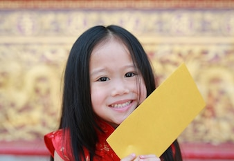 Close-up face of smiling little asian girl holding a gold envelope.