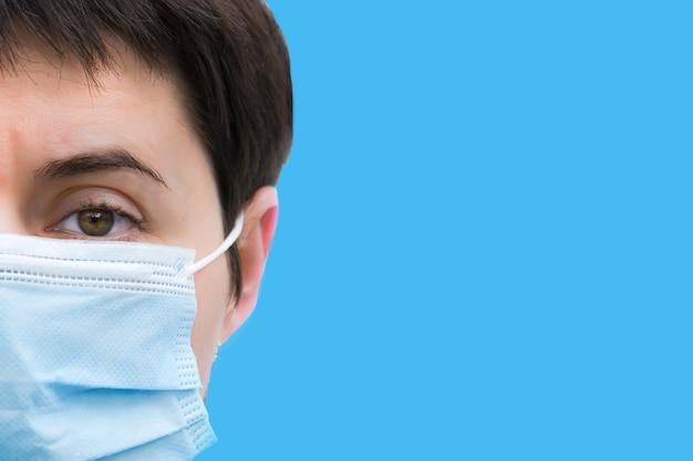 파란색 배경에 의료 일회용 마스크에 피곤 된 젊은 갈색 머리 여자의 클로즈업 얼굴. 열심히 일한 후 의료진의 피곤한 눈. 직접적이고 단호한 시선. 텍스트 오른쪽에 공백.
