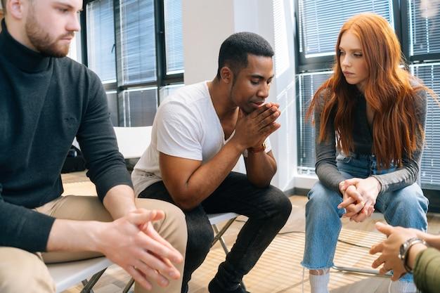 그룹 대인 치료 세션에 원에 앉아 문제를 공유하는 화가 난 아프리카계 미국인 청년의 클로즈업 얼굴. 우울한 흑인 남성이 다른 환자들에게 슬픈 이야기를 합니다.