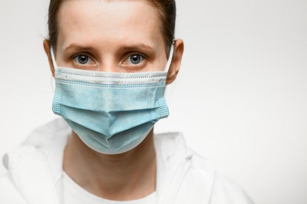 Сторона конца-вверх женщины в медицинской маске и белом защитном костюме на белом backgroung.