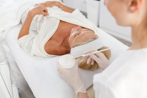 Закройте вверх по маске для пилинга, спа-косметологии, уходу за кожей. старшая женщина, получающая уход за лицом косметологом в спа-салоне, вид сбоку.