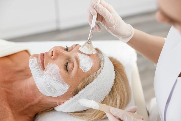 Закройте вверх по маске для пилинга, спа-косметологии, уходу за кожей. старшая женщина, получающая уход за лицом косметологом в спа-салоне.