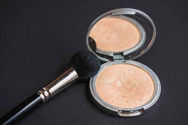 Close-up of face powder and brush on black backdrop