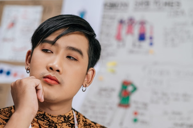 Close up face of professional asian young male tailor with measuring tape on neck thinking in studio.