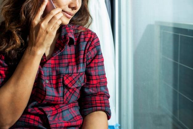クローズアップ顔悲しい女性は携帯電話を使用します。うつ病の感覚で一人でいてください。