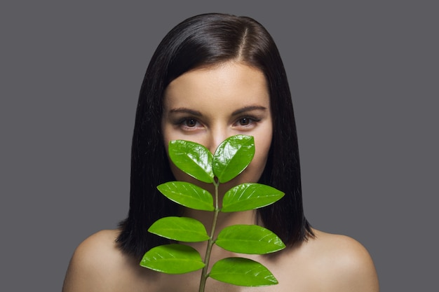 Close-up face of young beautiful woman with green leaf.