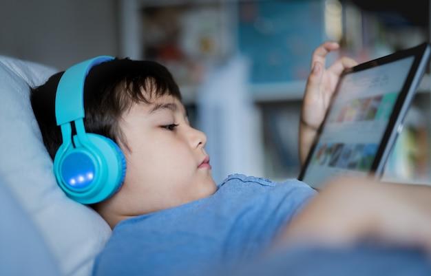 クローズアップ顔の少年はベッドに座って音楽を聴いてワイヤレスヘッドフォンを着用します