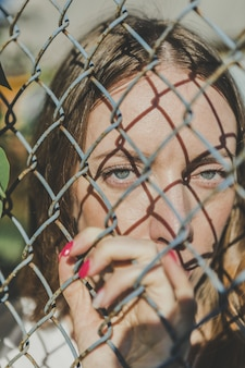 Close-up. the face of a young girl behind a metal fence