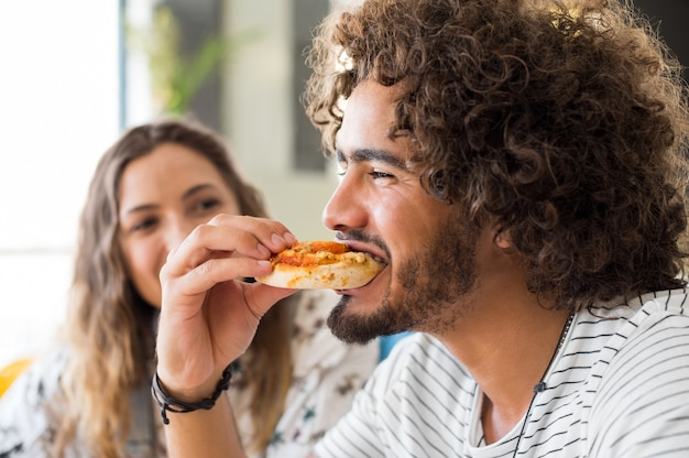 Close up face of a young man eating a pizza in a coffee shop