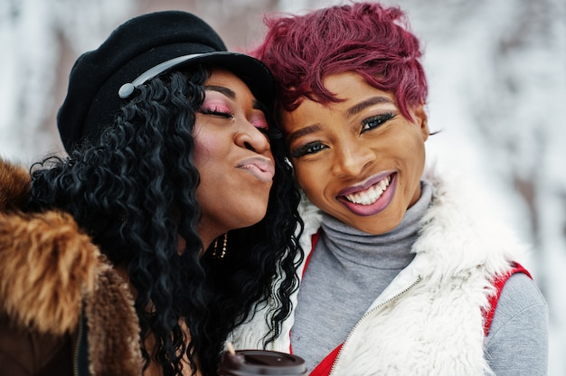 Close up faces of two african american women in sheepskin and fur coat posed at winter day