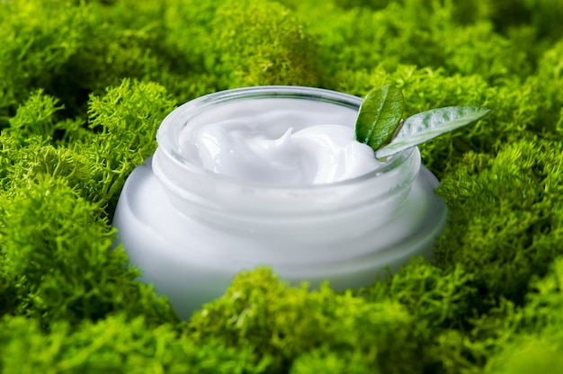 Close up of facial moisturizer in the middle of the moss.