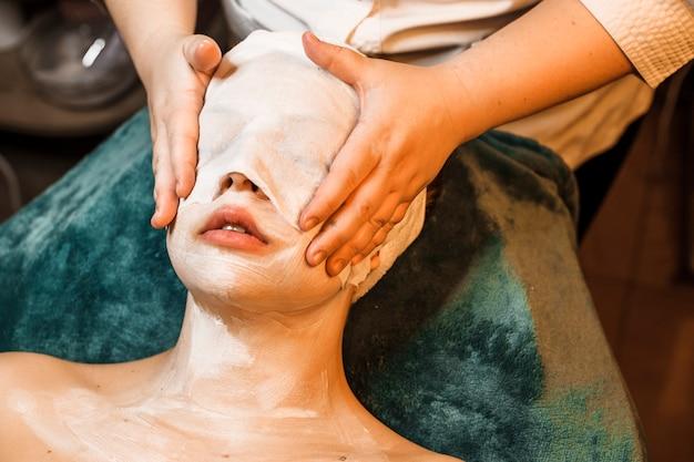 Завершите процедуру ухода за лицом на женском лице, используя белую маску anti age и прикрывая лицо белой тканью.
