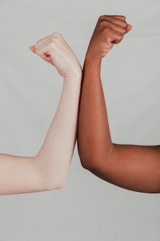 Close-up of fair and dark skinned women's hand flexing their fist against grey backdrop