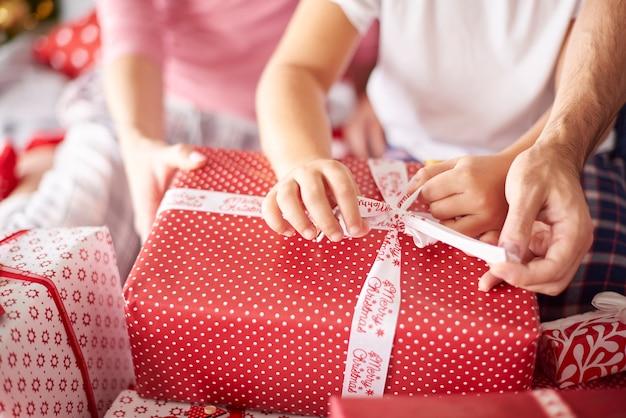 Primo piano delle mani della famiglia durante l'apertura dei regali di natale