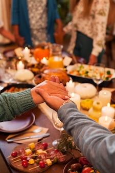 Семья крупным планом, взявшись за руки за ужином