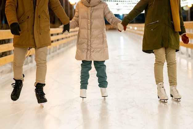 Close-up of family holding hands with child and skating on ice rink outdoors in winter