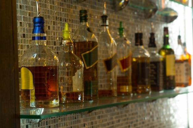 유리 스탠드에 있는 바에서 유명한 여러 병의 비싼 와인 디스플레이를 닫습니다.