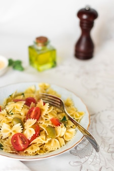 Close-up of farfalle pasta salad in white plate with fork on table cloth