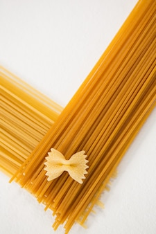 Close-up of farfalle and spaghetti pasta arranged on white background
