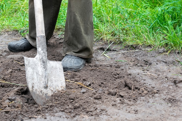Close up of farmer digging soil with shovel in rubber boots