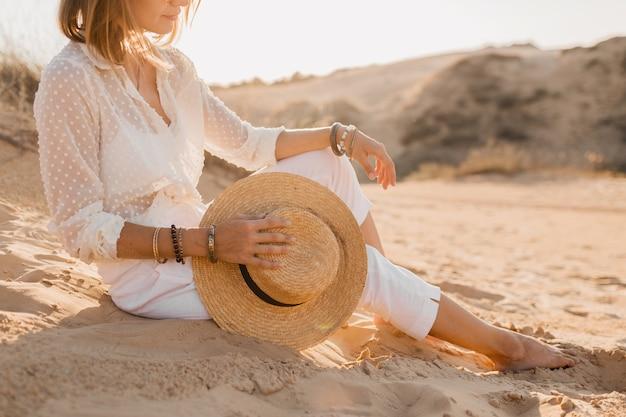 日没時に麦わら帽子を保持している白い服の砂漠のビーチでスタイリッシュな美しい女性のクローズアップファッションアクセサリー
