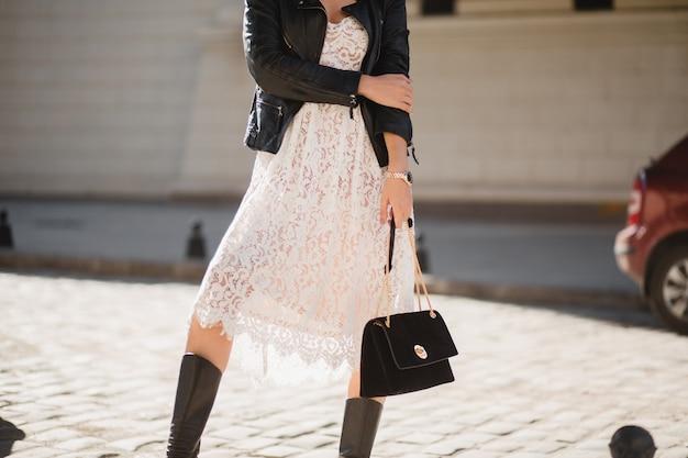 Chiudere i dettagli di moda della donna attraente che cammina in strada in abito alla moda che tiene la borsa, indossa una giacca di pelle nera, stile primavera autunno