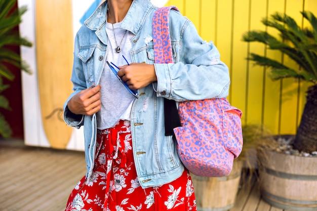 明るいトレンディな夏の春服、デニムジャケット、ヒョウ柄のバックパック、フローラルスカート、カジュアルなtシャツを着ている流行に敏感な女性のファッションの詳細を閉じます。
