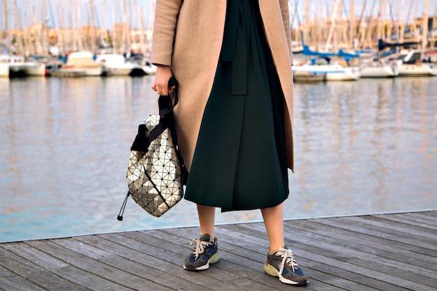 Закройте детали моды модной женщины, носящей элегантное платье, современные модные кроссовки и рюкзак с элегантным кашемировым пальто, позирующей на набережной в середине сезона, мягких пастельных тонах.