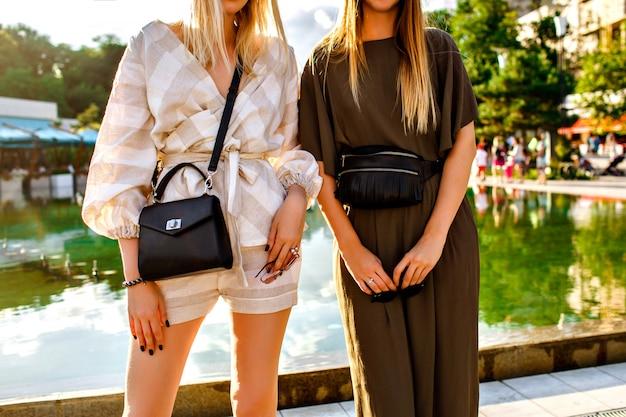 트렌디 한 정장, 고급 가방 및 액세서리를 착용 한 트렌디 한 여성의 패션 세부 정보를 닫습니다.
