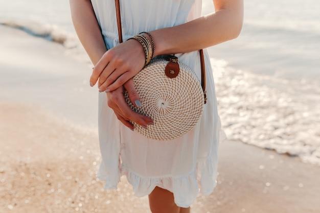 ビーチアクセサリーにわら財布バッグ夏スタイルの白いドレスを着た女性のファッションの詳細をクローズアップ