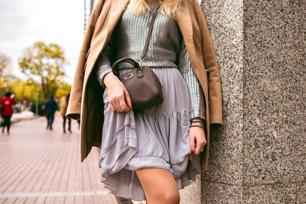 通りでポーズをとって、シルクのドレス、シルバーのセーター、クロスボディバッグ、豪華なカシミヤのコート、柔らかな色調、ジュエリー、アクセサリーを身に着けているエレガントな女性のファッションの詳細を閉じます。