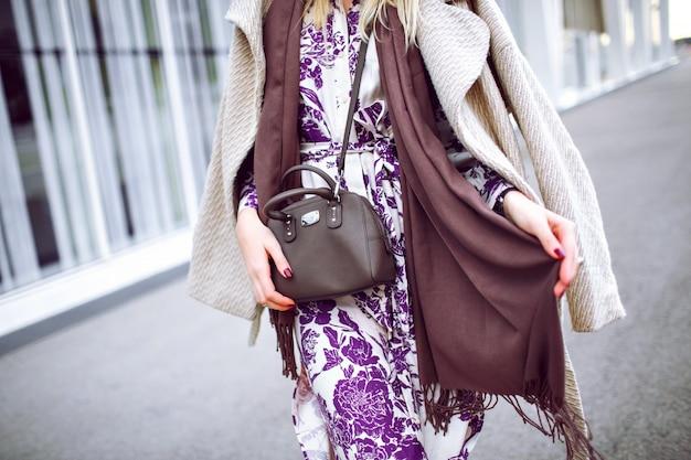 ファッションの詳細、トープ色のトレンディな色、エレガントなコートを着ている女性、花柄のマキシドレス、クロスボディバッグ、トレンディなアクセサリーとジュエリー、春の秋の時間、バーガンディのマニキュアを閉じます。