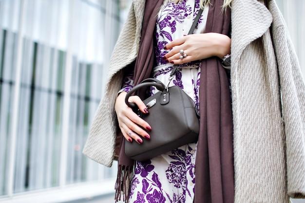 Primo piano dettagli di moda, colori di tendenza tortora, donna che indossa un cappotto elegante, maxi abito floreale, borsa a tracolla, accessori e gioielli alla moda, primavera autunno, manicure bordeaux.