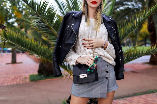 クローズアップファッションの詳細、トレンディでスタイリッシュな女性がヤシの木、ミニスカート、セーター、クロスボディバッグ、白いセーター、革のジャケット、ジュエリー、アクセサリー、モダンなストリートスタイルの近くの通りでポーズ