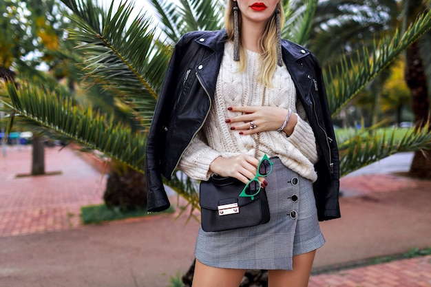 Close up fashion details, trendy stylish woman posing on the street near palm trees, mini skirt, sweater, cross body bag, white sweater, leather jacket, jewelry and accessories,modern street style