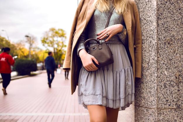 ファッションの詳細、ストリートでの女性の滞在、春の時間、シルクのドレスとカシミアのコート、シルバーのセーターとクロスボディバッグ、フェミニンでエレガントな魅力的な衣装をクローズアップ