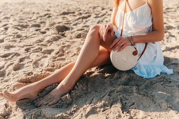 Close-up fashion details of woman in white dress with straw purse bag summer style on beach accessories
