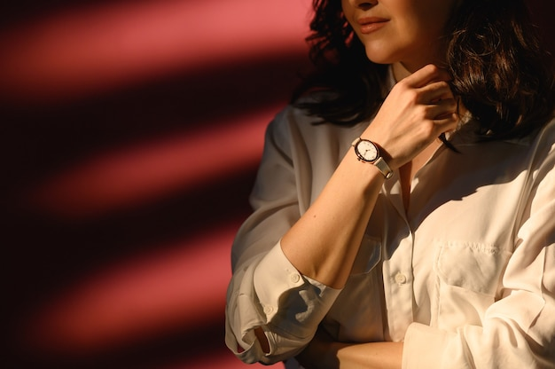 Close up fashion details, young business woman wearing golden watch and white shirt